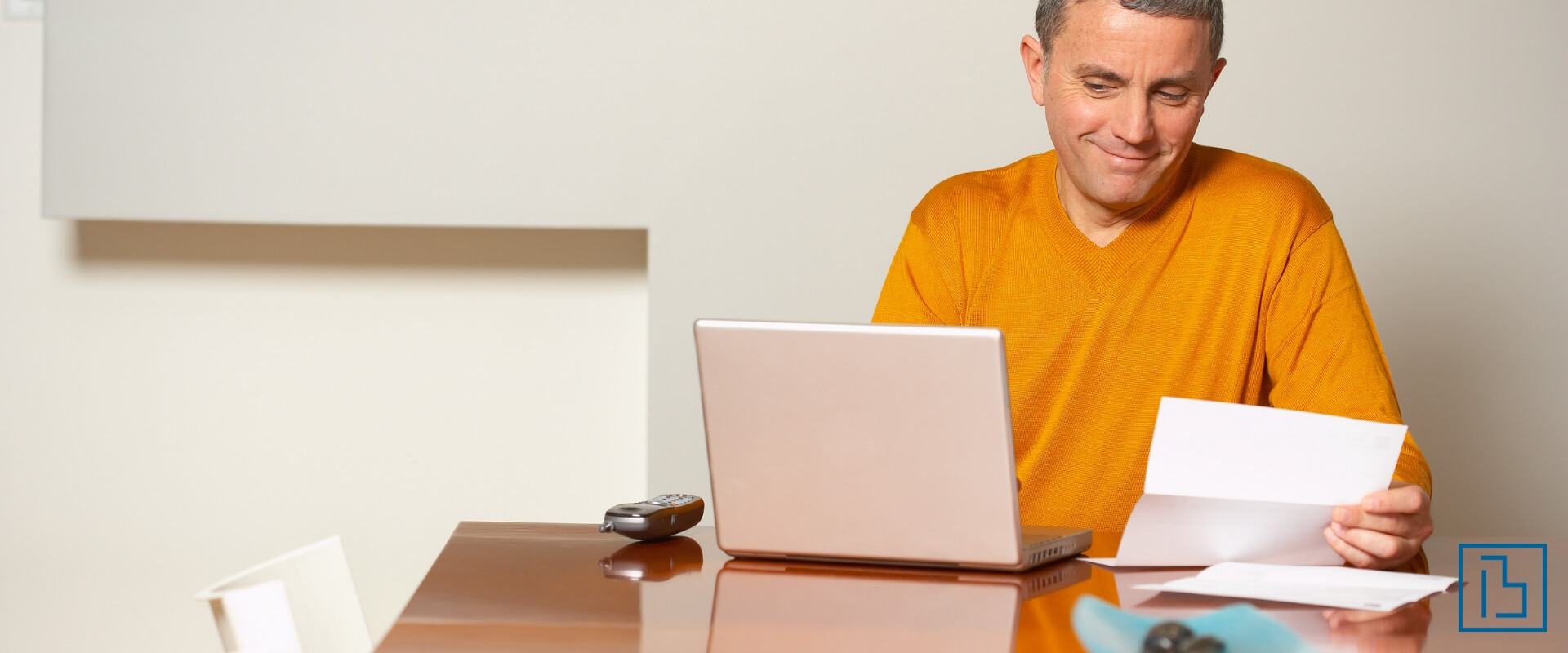 Man looking at letter and laptop - Beachworks LLC